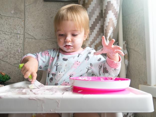 Nettes kind mit schmutzigem gesicht, das zu hause frühstückt und eine gabel in der hand hält