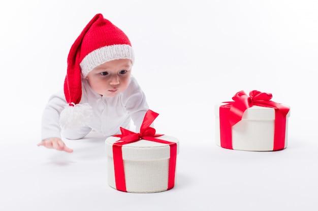 Nettes kind mit weihnachtsgeschenken und weihnachtsmann-hut