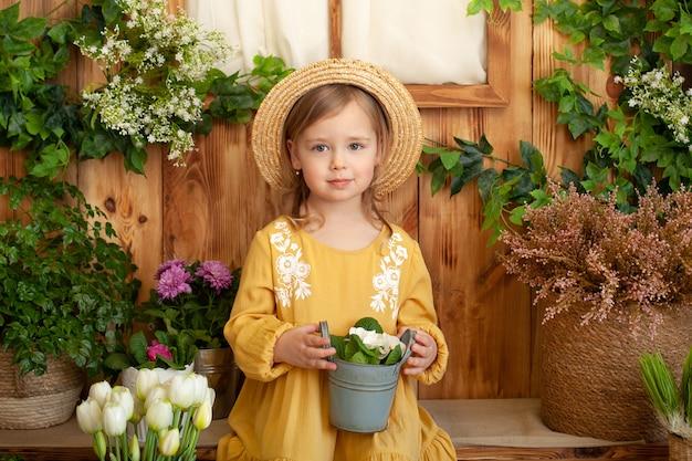Nettes kind spielt kleinen gärtner und pflanzt blumen in einem topf auf veranda des hauses. kleines mädchen im strohhut und kleid mit topfblumen im garten. glückliche kindheit. gartenarbeit. kind, das im hinterhof spielt