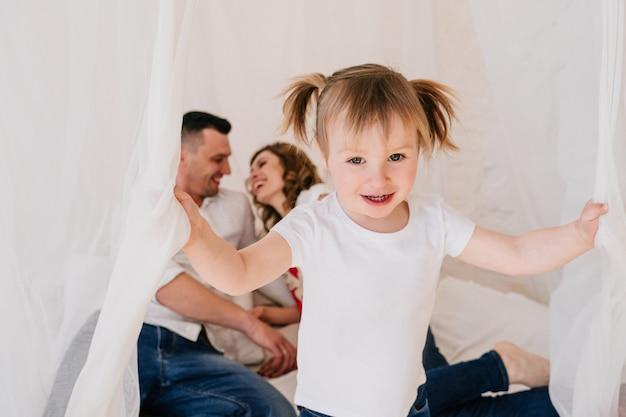 Nettes kind tochter und vater kitzeln mutter, die spaß gute zeit zusammen zu hause spielen, glückliche eltern und kleines kind mädchen genießen lustige aktivität und kommunikation, familie lachen entspannend