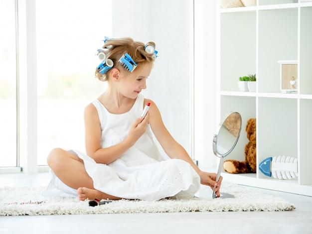Nettes kindermädchen, das roten lippenstift verwendet