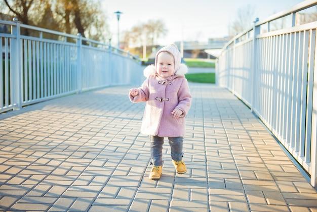 Nettes kindermädchen geht auf der brücke im herbstpark