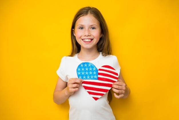 Nettes kindermädchen hält eine amerikanische flagge nahe ihrem herzen. patriotismus, unabhängigkeitstag, flag day konzept. gedenktag