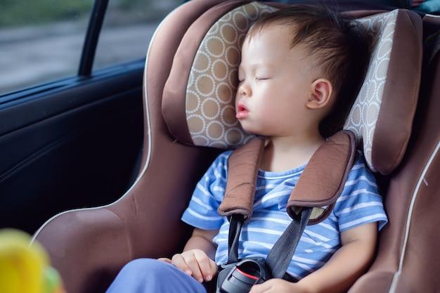 Nettes kleines asiatisches 1-jähriges kleinkindbabykind, das im modernen autositz schläft