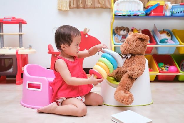 Nettes kleines asiatisches 18 monate altes kleinkindbaby, das auf töpfchen sitzt und ein buch im spielzimmer zu hause mit spielzeug & teddybär liest