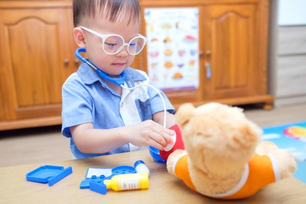 Nettes kleines asiatisches 2 jahre altes kleinkindjungenkind, das arzt mit plüschtier zu hause spielt, kind, das stethoskop hält, teddybärspielzeug untersuchen