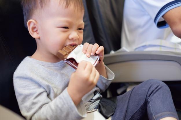 Nettes kleines asiatisches 2 jahre altes kleinkindjungenkind, das schokoriegel während des fluges im flugzeug isst. fliegen mit kindern konzept