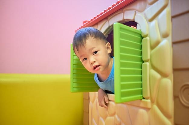 Nettes kleines asiatisches 2 jahre altes kleinkindjungenkind spielt blick ein boo vom fenster des plastikspielzeughauses,