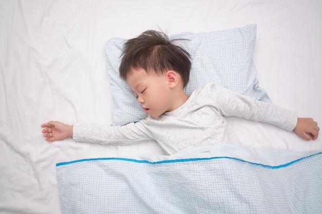 Nettes kleines asiatisches 3 - 4 jahre alte kleinkindjungenkind im pyjama ein schläfchen halten, schlafend auf seinem zurück auf weißem bettlaken im bett