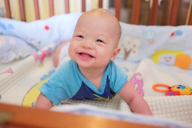 Nettes kleines asiatisches 5 - 6 monate alte babykind zur bauchzeit im babybett / in der krippe in der tageszeit des schlafzimmers zu hause; neugeborenes entspannendes kind. kindergarten für kleine kinder. weicher und selektiver fokus