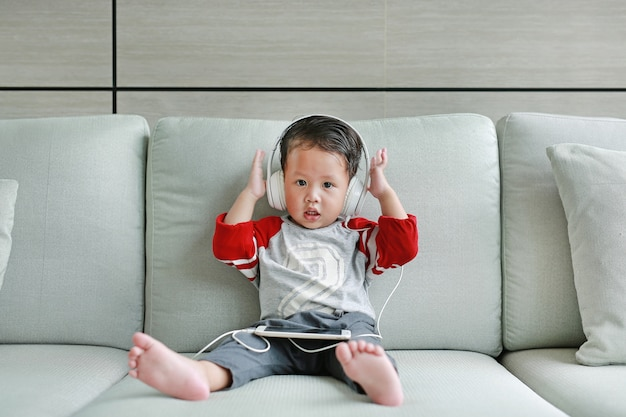 Nettes kleines asiatisches baby in den kopfhörern benutzt einen smartphone