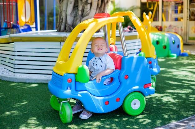 Nettes kleines asiatisches kind, das auf einem bunten spielzeugauto reitet
