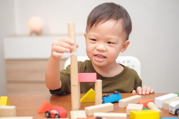 Nettes kleines asiatisches kind, das mit holzspielzeug spielt