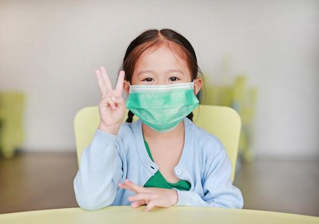 Nettes kleines asiatisches kindermädchen, das eine schutzmaske mit dem zeigen von drei fingern sitzt auf kinderstuhl im kinderraum trägt.