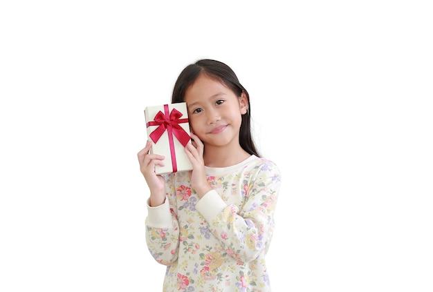 Nettes kleines asiatisches kindermädchen, das geschenkbox auf weiß hält