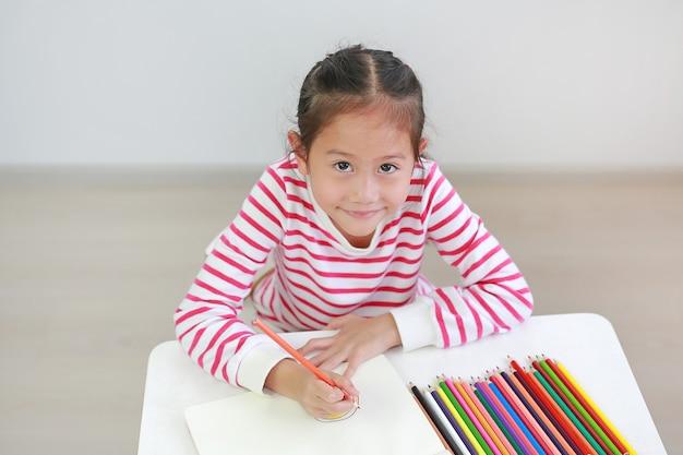 Nettes kleines asiatisches kindermädchen, das zu hause mit dem aufschauen zur kamera zeichnet