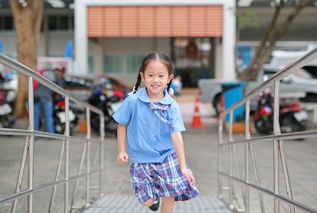 Nettes kleines asiatisches kindermädchen in der schuluniform, die herauf metalltreppe läuft.