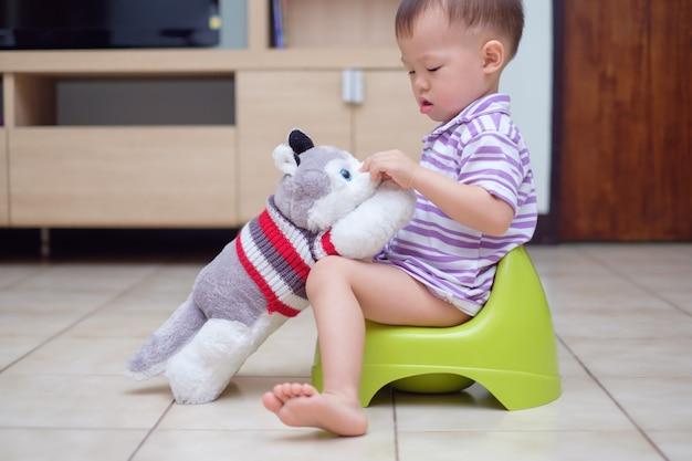 Nettes kleines asiatisches kleinkindbabykind, das auf töpfchen sitzt und mit seinem ausgestopften tierspielzeug des hundes spielt