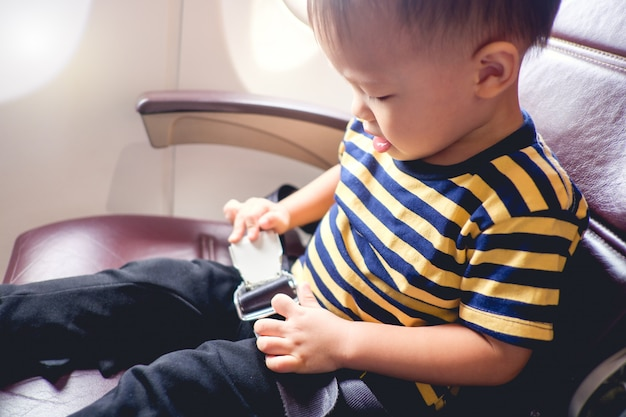 Nettes kleines asiatisches kleinkindjungenkind, das gestreiftes t-shirt trägt, schnallt sich an, während es auf flugzeugsitz sitzt. sicherheitsmaßnahmen an bord