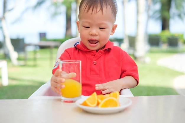 Nettes kleines asiatisches kleinkindjungenkind, das im hochstuhl sitzt und leckeres orangensaft kaltes getränk in einem glas während des frühstücks hält und trinkt