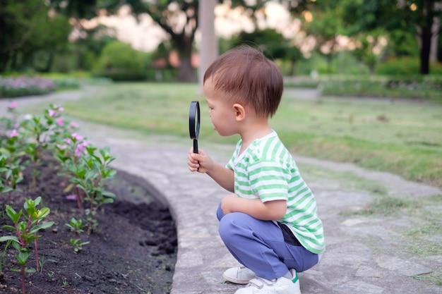 Nettes kleines asiatisches kleinkindjungenkind, das umgebung erkundet, indem man durch eine lupe im sonnenuntergang am schönen garten schaut