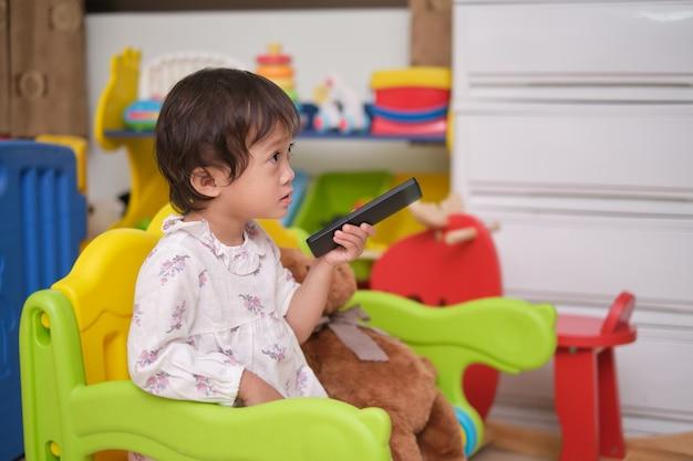 Nettes kleines asiatisches kleinkindmädchen, das die fernbedienung des fernsehers hält und im spielzimmer zu hause fernsieht