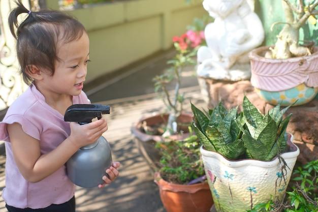 Nettes kleines asiatisches kleinkindmädchenkind, das spaß mit sprühflaschen-bewässerungspflanzen zu hause am sonnigen morgen hat, aufgaben für kinder, lernen zu hause