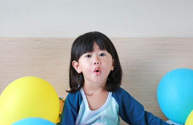 Nettes kleines asiatisches mädchen, das auf bett mit ballon spielt
