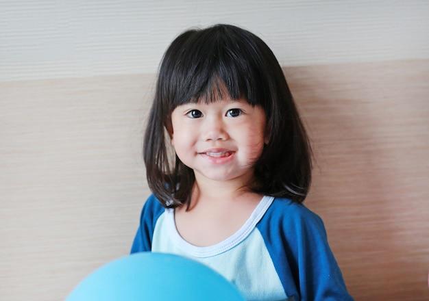 Nettes kleines asiatisches mädchen, das auf bett mit ballon spielt.
