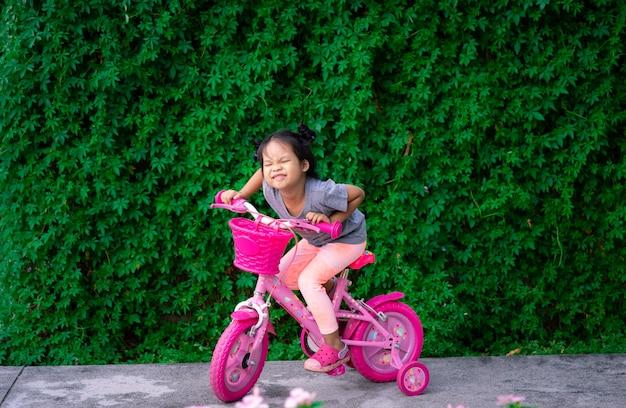 Nettes kleines asiatisches mädchen, das fahrrad fährt, um im park, im kindersport und im aktiven lebensstil zu üben