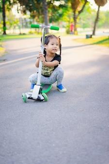 Nettes kleines asiatisches mädchen, das lernt, einen roller in einem park zu reiten