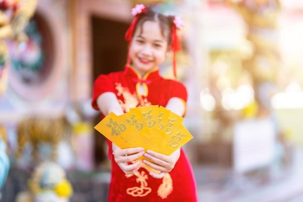 Nettes kleines asiatisches mädchen, das rotes traditionelles chinesisches cheongsam trägt, fokusshow, die gelbe umschläge in der hand für chinesisches neujahrsfest am chinesischen schrein hält