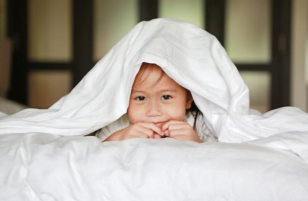 Nettes kleines asiatisches mädchen, das unter einer weißen decke auf dem bett spielt