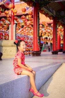 Nettes kleines asiatisches mädchen im chinesischen traditionellen kleid, das im tempel lächelt. frohes chinesisches neujahrskonzept.