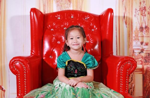 Nettes kleines asiatisches mädchen kleidete mit einer fantasieausstattung an, die auf dem roten sofa sitzt