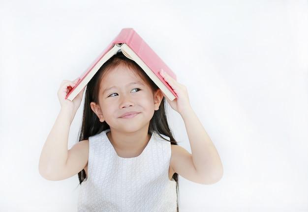 Nettes kleines asiatisches mädchenplatz-hardcover-buch auf ihrem kopf und auf weißem hintergrund oben schauen.