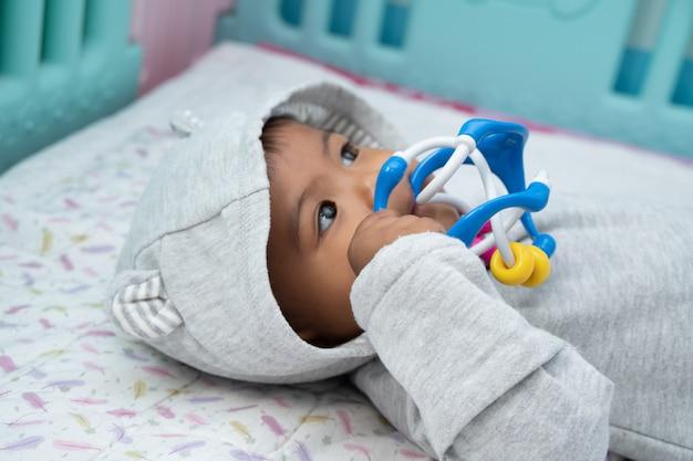 Nettes kleines asin baby, das auf weicher decke und spielspielzeug liegt