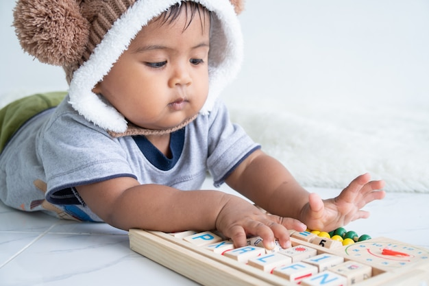 Nettes kleines asin baby, das mit hölzernem spielzeug spielt