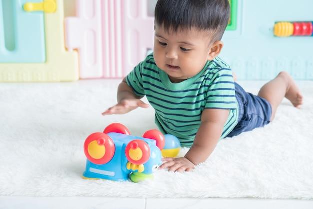Nettes kleines baby, das auf dem boden und spielspielzeugauto liegt
