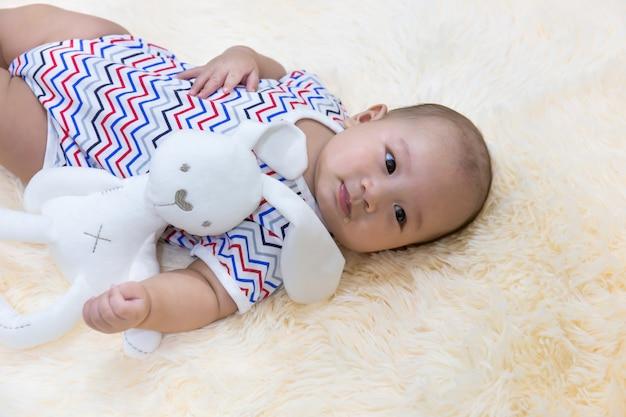 Nettes kleines baby, das auf weichem flaumigem silk teppich mit puppe schläft.