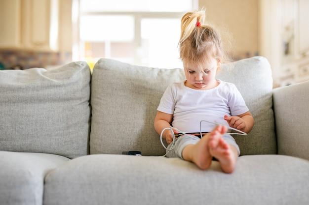 Nettes kleines baby, das digitale tablette spielt, die auf dem sofa sitzt. elternkontrolle. internet-sicherheitskonzept für kinder.