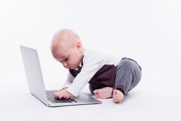 Nettes kleines baby, das im fort eines laptops sitzt
