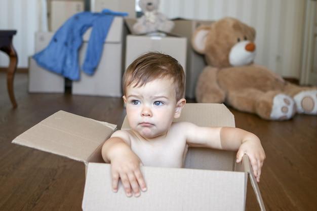 Nettes kleines baby, das innerhalb der pappschachtel träumt von seinem zukünftigen haus sitzt