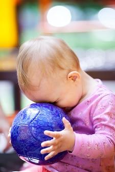 Nettes kleines baby, das mit einem ball spielt
