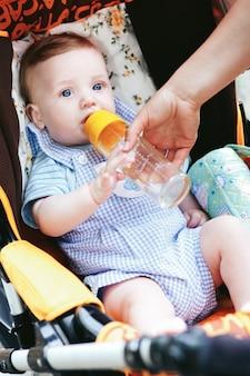 Nettes kleines baby der blauen augen mit flasche im spaziergänger