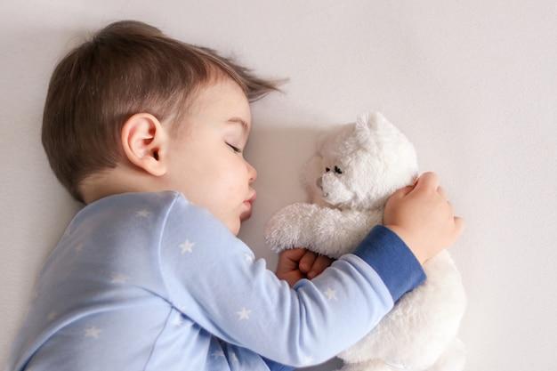 Nettes kleines baby in den hellblauen pyjamas schlafend, weißes weiches teddybärspielzeug umarmend.