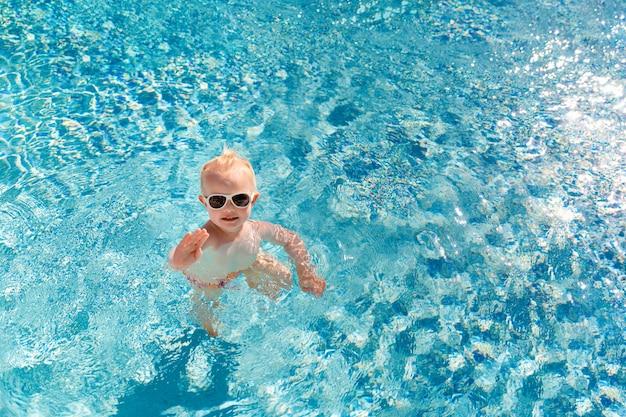 Nettes kleines baby in der sonnenbrille schwimmend im pool und seine hand wellenartig bewegend.