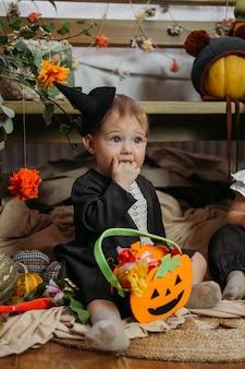 Nettes kleines baby in halloween-kostüm gekleidet, das zu hause auf dem bett mit halloween-dekoration sitzt
