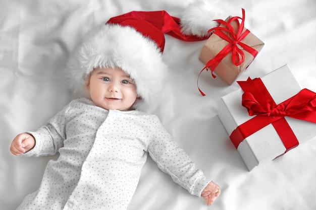 Nettes kleines baby in weihnachtsmütze und geschenkboxen auf weißem blatt