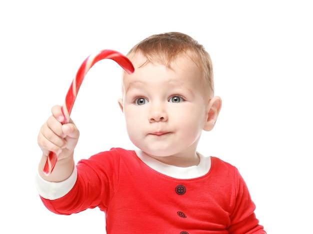 Nettes kleines baby mit zuckerstange auf weißem hintergrund. weihnachtskonzept